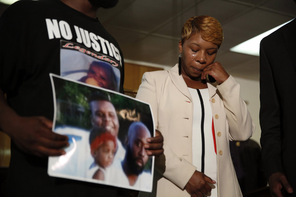 Photo - FILE - In this Aug. 11, 2014 file photo, Lesley McSpadden, the mother of 18-year-old Michael Brown, wipes away tears as Brown's father, Michael Brown Sr., holds up a family picture of himself, his son, top left, and a young child during a news conference in Jennings, Mo. Lingering questions about Michael Brown could be answered Wednesday as two news organizations seek the release of any possible juvenile records for the unarmed 18-year-old who was shot by a police officer last month.(AP Photo/Jeff Roberson, File)