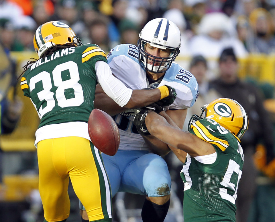 Photo - Green Bay Packers' Tramon Williams (38) and Brad Jones (59) break up a pass intended for Tennessee Titans' Craig Stevens (88) during the second half of an NFL football game Sunday, Dec. 23, 2012, in Green Bay, Wis. (AP Photo/Mike Roemer)