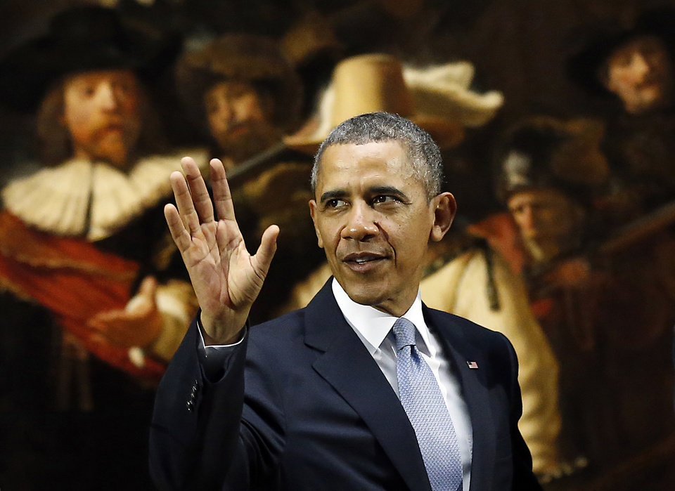 Photo - U.S. President Barack Obama waves in front of  Dutch master Rembrandt's The Night Watch painting during a visit to the Rijksmuseum in Amsterdam, Netherlands, Monday, March 24, 2014. Obama will attend the two-day Nuclear Security Summit in The Hague. (AP Photo/Frank Augstein)