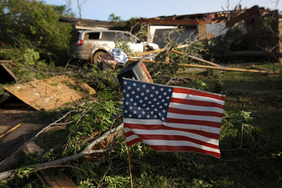 Photo - An American flag blows in the wind outside a  home that was struck by a tornado in Woodward, Okla., Sunday, April 15, 2012. Photo by Bryan Terry