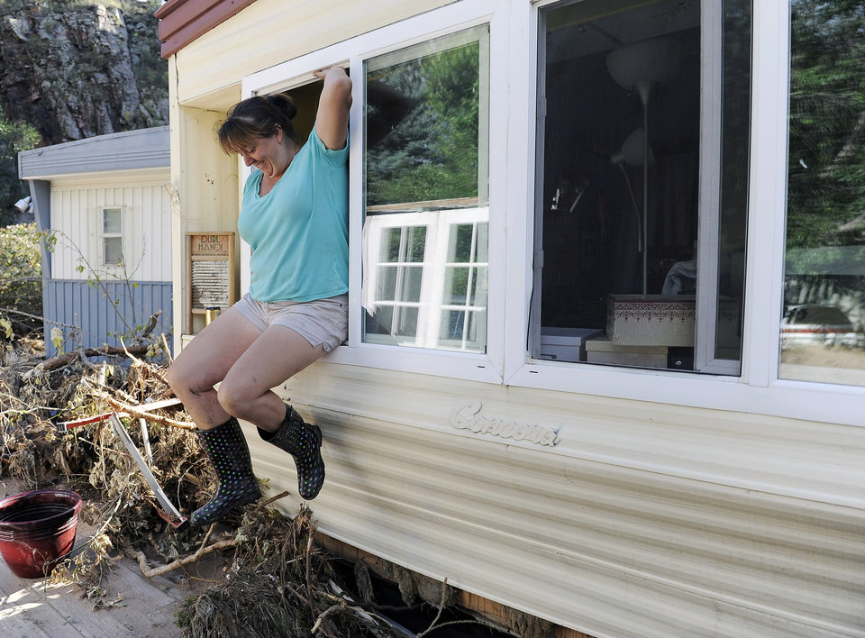 Photo - Risa Vandenbos jumps out the window of her flood-damaged trailer at the River Bend Mobile Home Park in Lyons, Colo., on Thursday, Sept. 19, 2013. Vandenbos was gathering belongings that were salvageable from her trailer. Hundreds of evacuees were allowed past National Guard roadblocks Thursday to find a scene of tangled power lines, downed utility poles, and mud-caked homes and vehicles. (AP Photo/Chris Schneider)