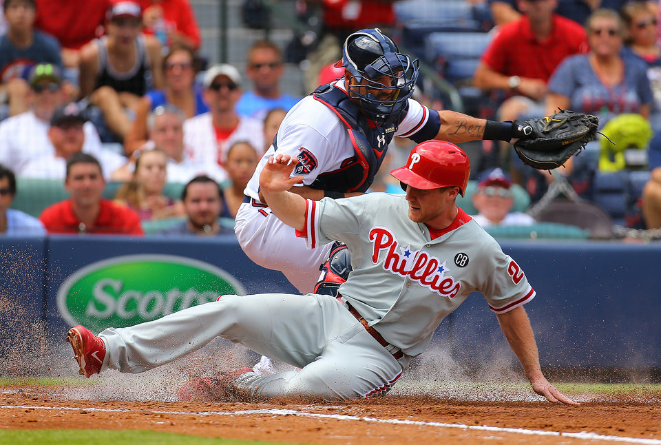 Photo - Philadelphia Phillies' Cody Asche (25) scores on a Ben Revere sacrifice fly as Atlanta Braves catcher Gerald Laird (11) handles the late throw in the third inning of a baseball game Monday, Sept. 1, 2014, in Atlanta.   (AP Photo/Atlanta Journal-Constitution, Curtis Compton)  MARIETTA DAILY OUT; GWINNETT DAILY POST OUT; LOCAL TELEVISION OUT; WXIA-TV OUT; WGCL-TV OUT )