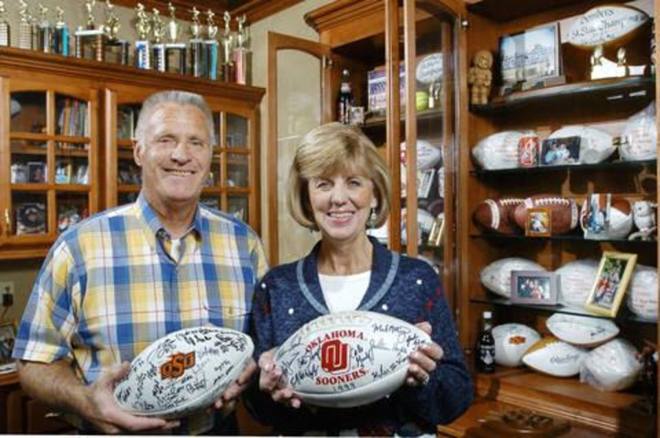 Photo - Ray and Judy Gundy  in a room of their Midwest City home where much of the memorabilia from their two sons', Cale and Mike, athletic careers are kept. Staff photo by Jim Beckel.