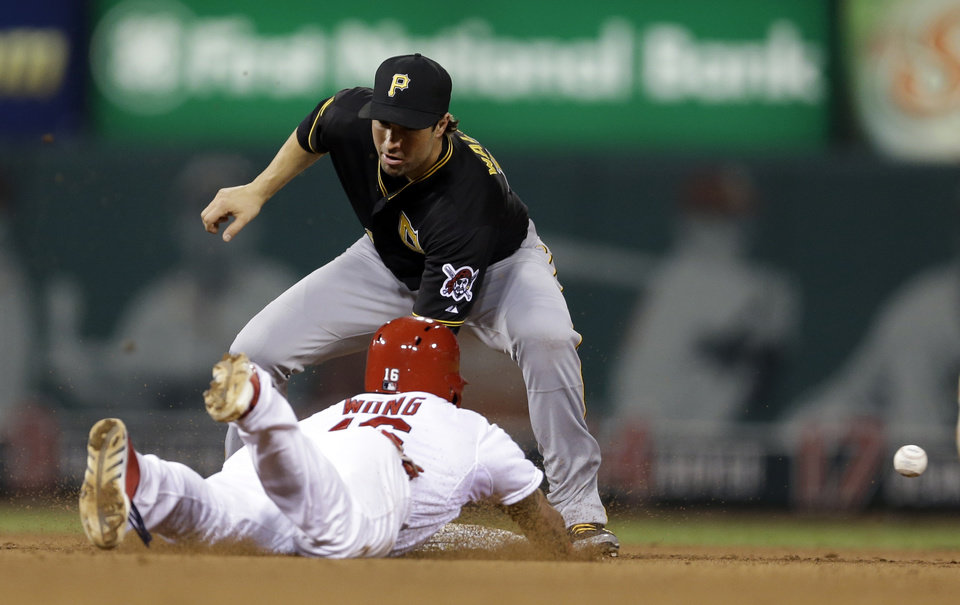 Photo - St. Louis Cardinals' Kolten Wong, bottom, is safe at second for a stolen base as the throw gets away from Pittsburgh Pirates second baseman Neil Walker during the fifth inning of a baseball game Wednesday, July 9, 2014, in St. Louis. Wong went on to third and Pirates catcher Chris Stewart was charged with a throwing error on the play. (AP Photo/Jeff Roberson)