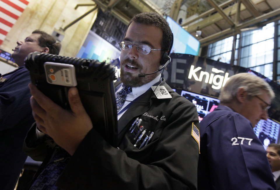 Photo -   FILE-In this Friday Sept. 7, 2012, file photo, trader Richard Scardino, center, works on the floor of the New York Stock Exchange. Stocks edged higher during trading on Wednesday, Sept. 12, 2012. Investors were happy to see that Germany's highest court cleared the way for that country to participate in a European rescue fund. Attentions now shift to the Federal Reserve, which wraps up its two-day meeting Thursday. (AP Photo/Richard Drew, File)