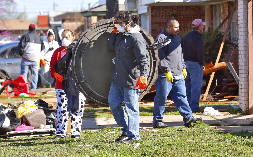 Photo - Residents come together to help clean up storm damage to a home in Moore, Okla. on Thursday, March 26, 2015. A tornado hit the area on Wednesday evening causing damage in the area.  Photo by Chris Landsberger, The Oklahoman