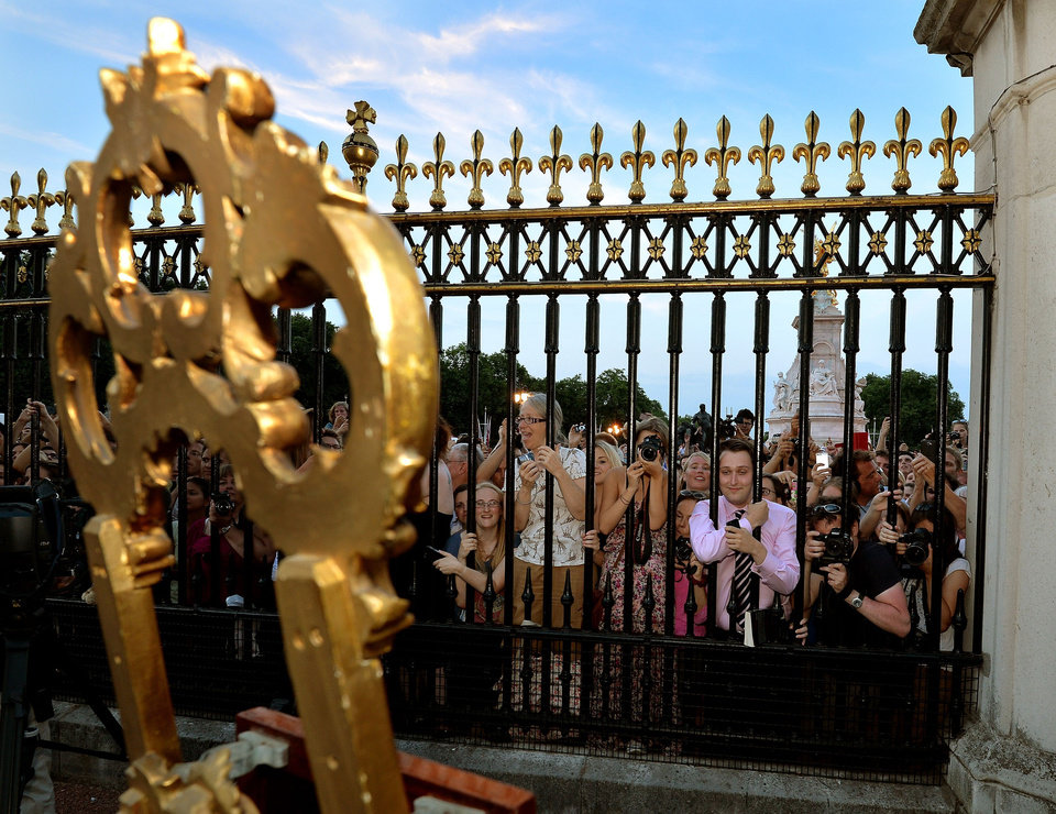 The large waiting crowds cheers as they read the news on an easel in the forecourt of Buckingham Palace, to announce the birth of a baby boy, at 4.24pm to William and Kate, the Duke and Duchess of Cambridge at St Mary\'s Hospital in west London, Monday July 22, 2013. The notification was set up on an easel facing the gates for public view. The child is now third in line to the British throne. (AP Photo/John Stillwell, Pool)