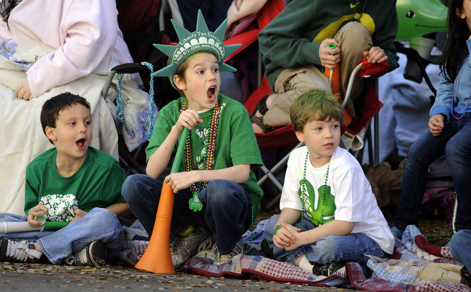 Photo - Jacob Tidwell, center, and his friends Donavan Mock, left, and Preston Vasquez react to a band during Savannah's 189-year-old St. Patrick's Day parade, Saturday, March 16, 2013, in Savannah, Ga. Started in 1824 by early Irish immigrants to Georgia, the parade has ballooned into a sprawling street party that makes for Savannah's most profitable tourism event. (AP Photo/Stephen Morton)