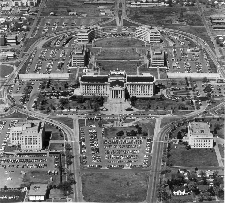 Photo - AERIAL VIEWS--Ringed by a maze of roadways and parking lots is the Oklahoma State Capitol Building, sitting at the base of a horseshoe-shaped array of office buildings. Cars and school buses compete for parking space around the state's seat of power during the legislative session.  Staff Photo by Al McLaughlin taken 3/29/77.