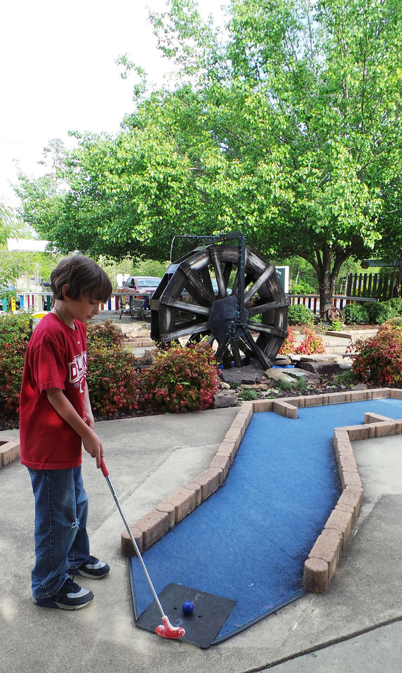 Photo - Ramey Brinkman, then 8, putts during a round of miniature golf at Hochatown Amusements. PHOTO BY LILLIE-BETH BRINKMAN, THE OKLAHOMAN.