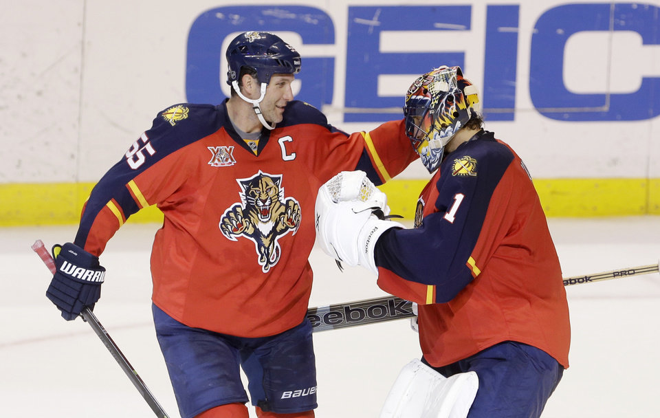 Photo - Florida Panthers defenseman Ed Jovanovski (55) celebrates with goalie Roberto Luongo (1) after the Panthers defeated the Ottawa Senators 3-2 in a shootout during an NHL hockey game, Tuesday, March 25, 2014 in Sunrise, Fla. (AP Photo/Wilfredo Lee)