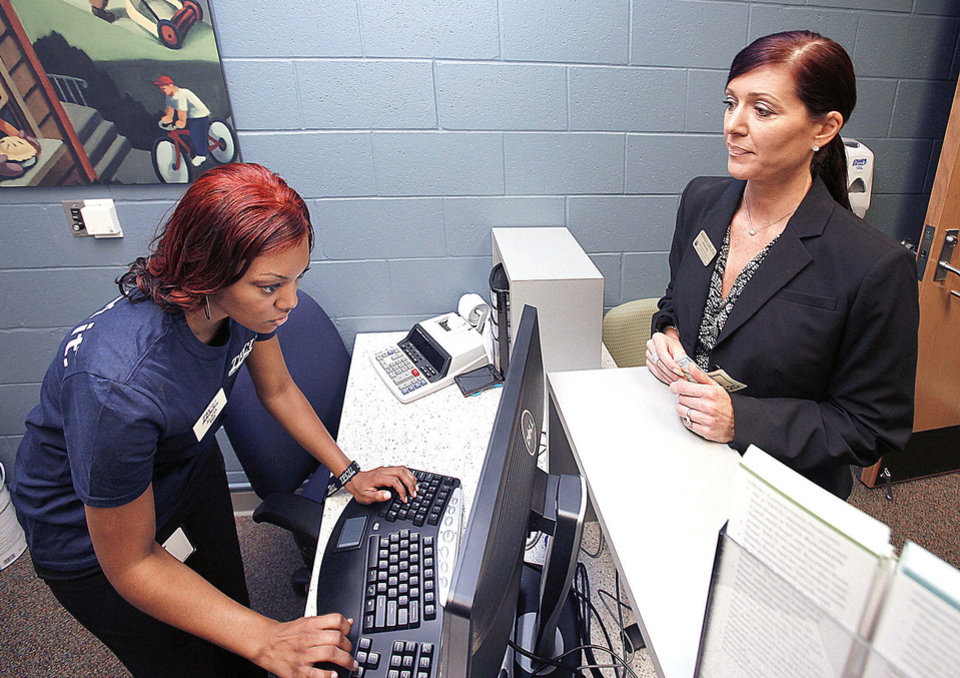 Photo - Student Intern Trainer Alicia Arterberry assists John Marshall High School Principal Aspasia Carlson as she becomes the first person to open a new account after the opening of a Tinker Federal Credit Union branch at the school in Oklahoma City, OK, Monday, August 6, 2012,  By Paul Hellstern, The Oklahoman