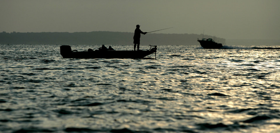Photo - A striper fisherman tries his luck in the early morning hours as the sun rises on Lake Texoma. Photo by Bryan Terry, The Oklahoman Archive
