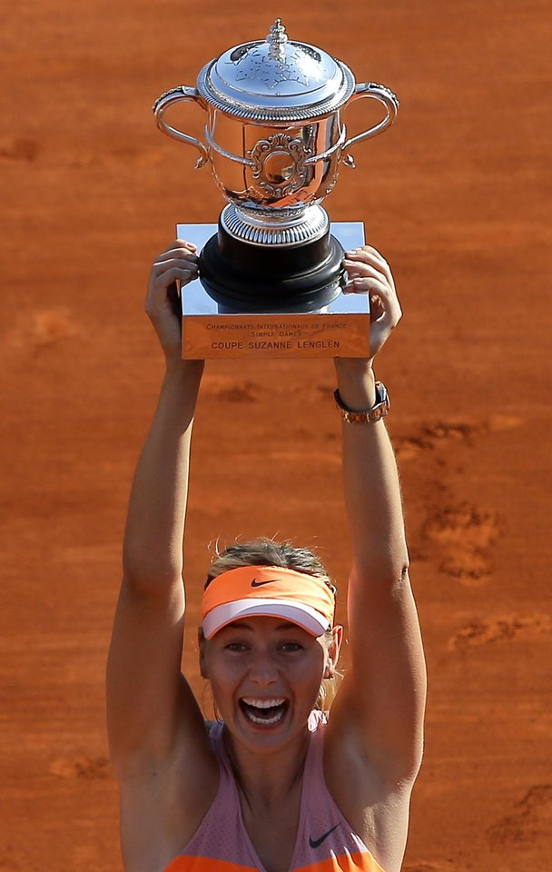 Photo - Russia's Maria Sharapova holds her trophy after winning the women's final match of  the French Open tennis tournament against Romania's Simona Halep at the Roland Garros stadium, in Paris, France, Saturday, June 7, 2014. Sharapova won 6-4, 6-7, 6-4.  (AP Photo/Michel Spingler)