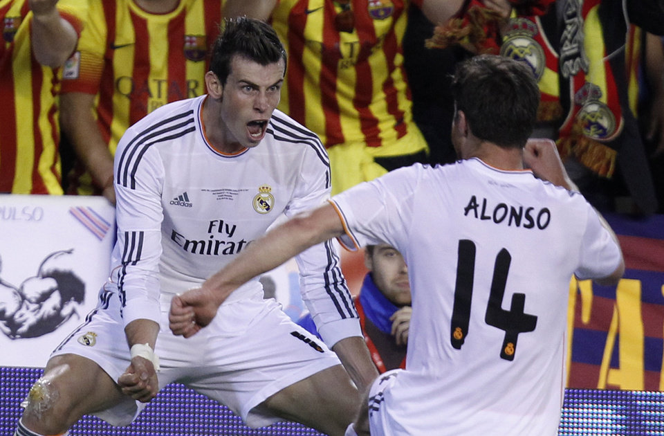 Photo - Real's Gareth Bale, left celebrates with Xabi Alonso after scoring his team's 2nd goal during the final of the Copa del Rey between FC Barcelona and Real Madrid at the Mestalla stadium in Valencia, Spain, Wednesday, April 16, 2014. (AP Photo/Alberto Saiz)