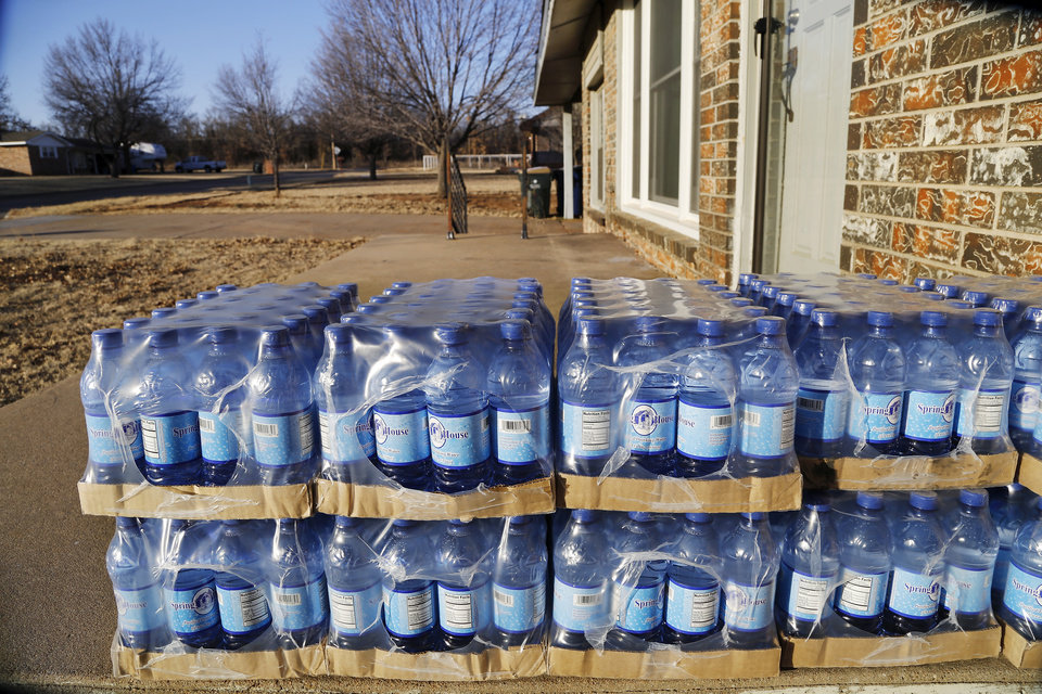 Photo - Cases of bottled water are stacked on the front porch of this house on Quail Drive in Duncan. The water is delivered to residents in the neighborhood by Halliburton. Halliburton in Duncan on Jan. 20, 2014.  Photo by Jim Beckel, The Oklahoman