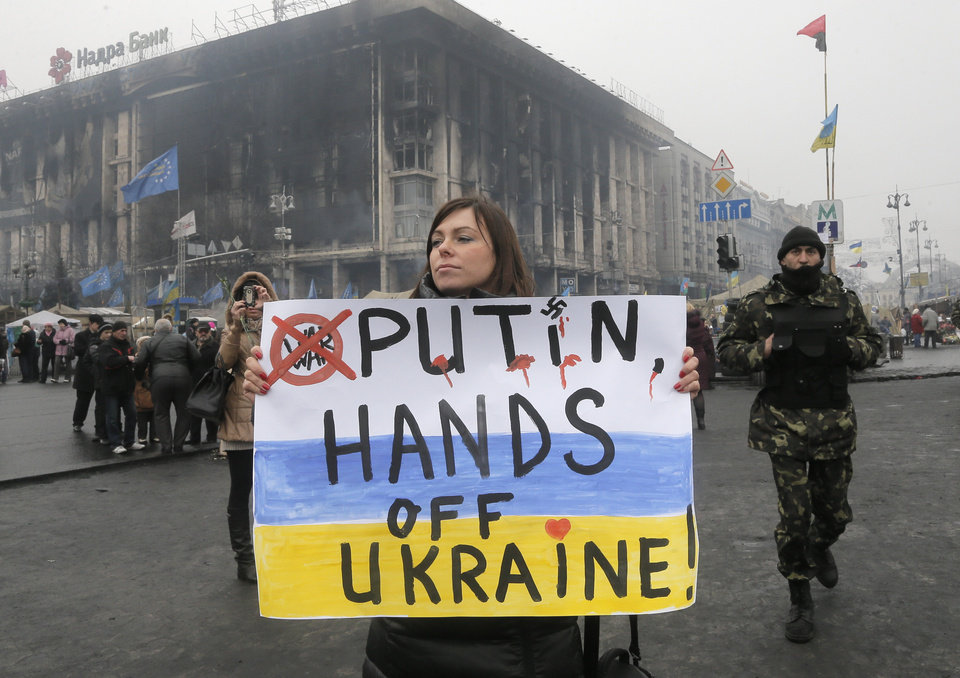 Photo - A woman holds a poster against war at Kiev's Independence Square, in Ukraine, Thursday, March 6, 2014. The  Heads of State of the EU will meet Thursday in emergency session in Brussels to discuss the situation in Ukraine. The destroyed trade union offices which was burned in clashes seen in the background  (AP Photo/Efrem Lukatsky)