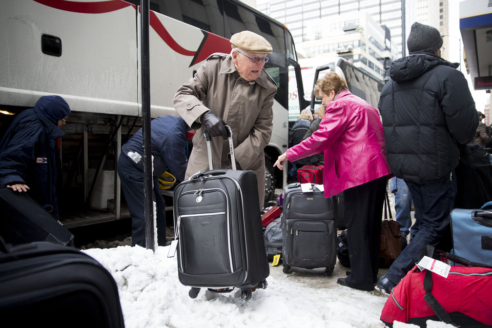 Photo - Passengers unload their luggage after arriving at Union Station after their Amtrak train from Los Angeles became stuck in snow drifts on Tuesday, Jan. 7, 2014, in Chicago. The severe weather forced hundreds of Amtrak passengers to spent the night onboard three trains stranded due to the snow in northern Illinois. (AP Photo/Andrew A. Nelles)