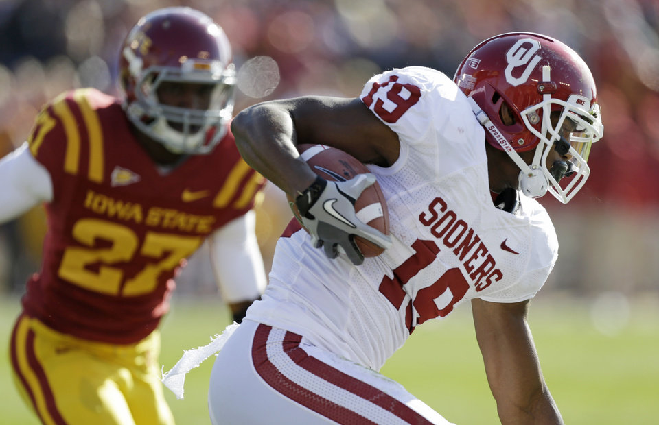 Photo - Oklahoma wide receiver Justin Brown, right, runs from Iowa State linebacker C.J. Morgan, left, after making a reception during the first half of an NCAA college football game, Saturday, Nov. 3, 2012, in Ames, Iowa.  Oklahoma won 35-20. (AP Photo/Charlie Neibergall) ORG XMIT: IACN121