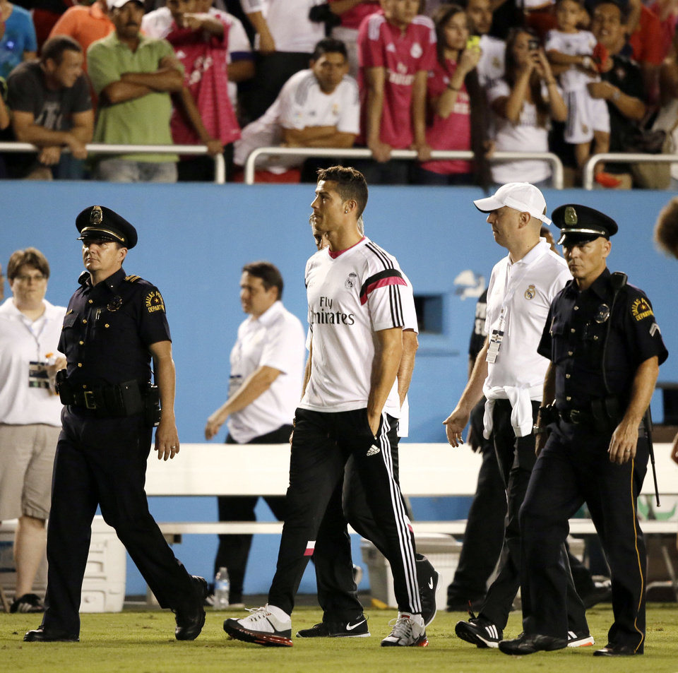 Photo - Real Madrid's Cristiano Ronaldo is escorted by police officers as he walks off the field with his team following their 1-0 loss to Roma in a Guinness International Champions Cup soccer tournament match, Tuesday, July 29, 2014, in Dallas. (AP Photo/Tony Gutierrez)