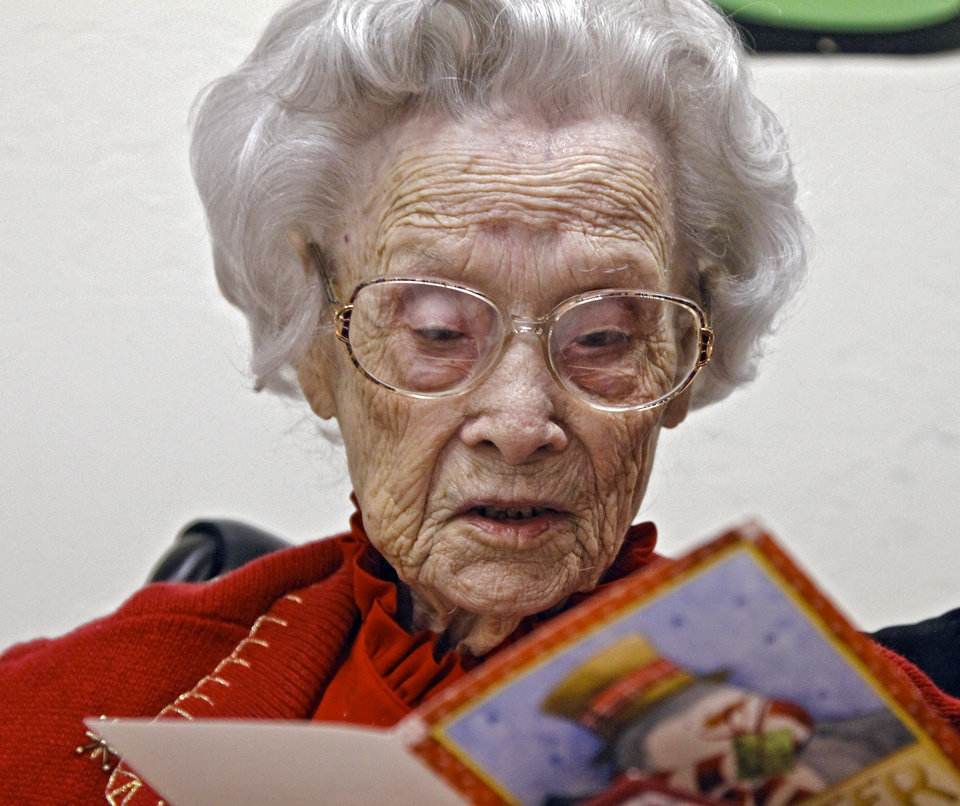Photo - Ora E. Holland reads her birthday card as she has an early birthday celebration at Heritage Assisted Living Center on Saturday, Dec. 22, 2012, in Oklahoma City, Okla. Holland will celebrate her 112th birthday on Dec. 24, 2012.   Photo by Chris Landsberger, The Oklahoman
