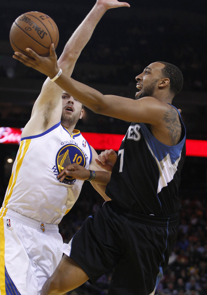 Photo - Minnesota Timberwolves' Derrick Williams, right, shoots as Golden State Warriors' David Lee defends during the first half of an NBA basketball game, Tuesday, April 9, 2013, in Oakland, Calif. (AP Photo/George Nikitin)
