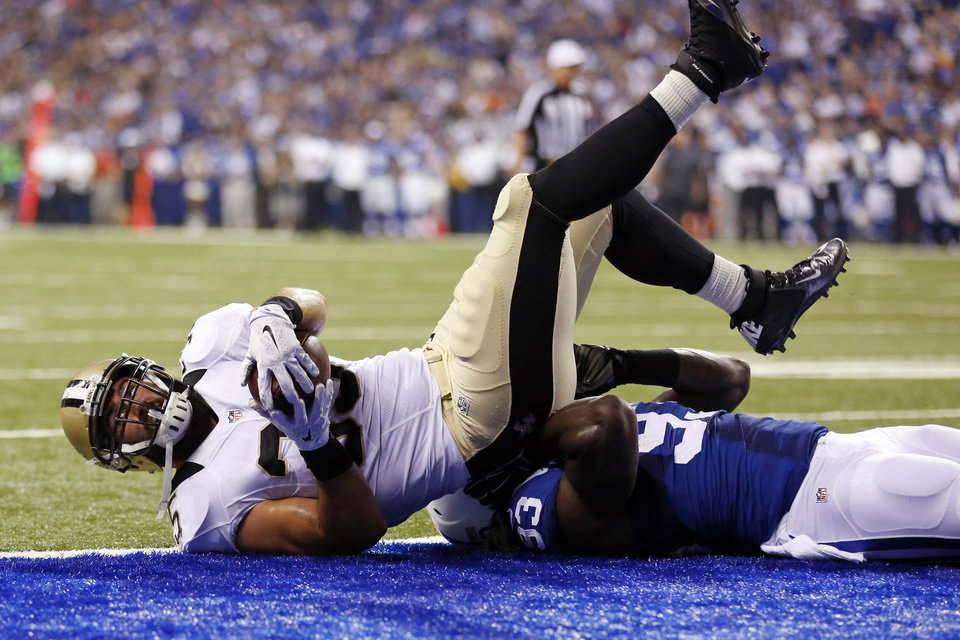 Photo - New Orleans Saints fullback Austin Johnson, top, goes over Indianapolis Colts outside linebacker Erik Walden for a touchdown during the first half of an NFL preseason football game in Indianapolis, Saturday, Aug. 23, 2014. (AP Photo/Sam Riche)