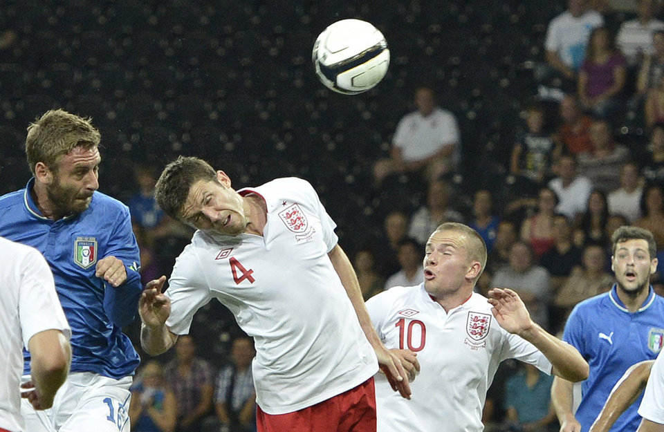 Photo -   Italy's Daniele De Rossi, left, scores the opening goal past England's Michael Carrick, center, and Tom Cleverly during an international friendly test match between the national soccer teams of Italy and England at the Stade de Suisse stadium in Bern, Switzerland, Wednesday, Aug. 15, 2012. (AP Photo/Keystone, Peter Schneider)