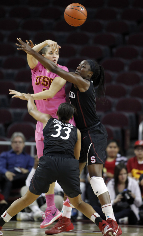 Photo - Southern California guard Jordan Adams, left, passes the ball away from Stanford guard Amber Orrange (33) and forward Chiney Ogwumike, right, during the first half of an NCAA college basketball game Friday, Feb. 21, 2014, in Los Angeles. (AP Photo/Alex Gallardo)