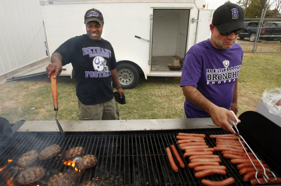 Photo - Tino Vann, left, and Jimmy Seeds cook burgers and hot dogs for the crowd during a high school football scrimmage between Bethany and Jones at Bethany Bronco Stadium, Thursday, August 22, 2012. Photo by Doug Hoke, The Oklahoman.