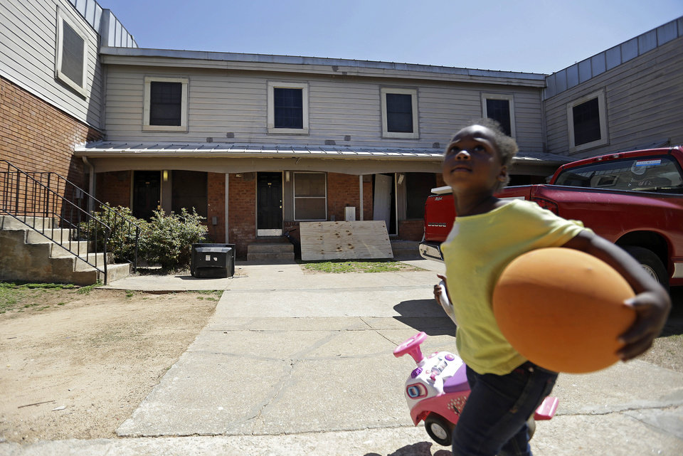 Photo - A child walks past the Atlanta, Ga., apartment, second door on left, on Thursday, April 10, 2014, where federal agents rescued Frank Arthur Janssen, of Wake Forest. N.C. The five people accused of kidnapping Janssen sent his wife a picture of him tied up in the Atlanta apartment and threatened to torture and dismember him, authorities said Thursday. John Strong, FBI special agent in charge in North Carolina, said the kidnapping of Janssen was related to his daughter's prosecution of North Carolina prisoner Kelvin Melton, who is serving a life sentence for his 2012 conviction for being a habitual felon. (AP Photo/David Goldman)