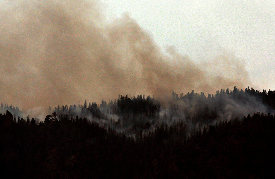 The Squirrel Creek Fire burns along the ridge line of Sheep Mountain on Monday, July 2, 2012, southwest of Laramie, Wyo. Crews in Wyoming faced erratic winds and dry, fire-fueling conditions Monday as they fought three large forest fires that have forced hundreds of evacuations across the state. (AP Photo/The Casper Star-Tribune, Alan Rogers)