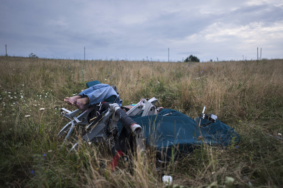 Photo - A body sitting in a plane chair is placed at the crash site of a Malaysia Airlines jet near the village of Hrabove, eastern Ukraine, Saturday, July 19, 2014. World leaders demanded Friday that pro-Russia rebels who control the eastern Ukraine crash site of Malaysia Airlines Flight 17 give immediate, unfettered access to independent investigators to determine who shot down the plane. (AP Photo/Evgeniy Maloletka)