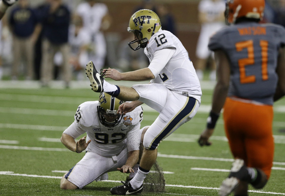 Photo - Pittsburgh's Chris Blewitt (12) kicks the go-ahead field goal from the hold of Matt Yoklic during the fourth quarter of the Little Caesars Pizza Bowl NCAA college football game against Bowling Green on Thursday, Dec. 26, 2013, in Detroit. Pittsburgh won 30-27. (AP Photo/Carlos Osorio)