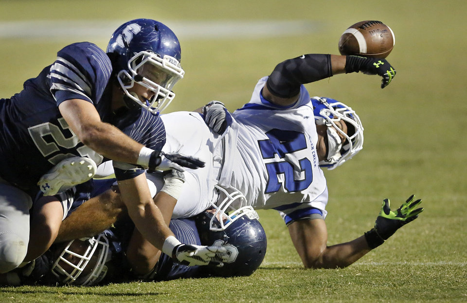 The football pops out of the hands of Deer Creek running back Alec James after he was brought to the ground by three Shawnee tacklers, including linebacker Matt Daniel, left,  during high school football game between the Shawnee Wolves and the Deer Creek Antlers  at Harris Stadium in Shawnee, Friday night, Sep. 13, 2013. Officials on the field the fumble came after James was on the turf. Deer Creek scored a touchdown a few plays later.   Photo  by Jim Beckel, The Oklahoman.