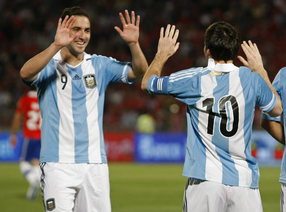 Photo -   Argentina's Gonzalo Higuain celebrates with Lionel Messi, right, after scoring against Chile during a World Cup 2014 qualifying soccer match in Santiago, Chile, Tuesday, Oct. 16, 2012. (AP Photo/Luis Hidalgo)