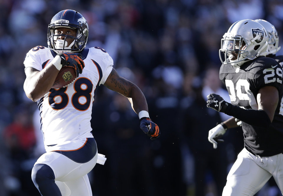 Photo - Denver Broncos wide receiver Demaryius Thomas (88) runs past Oakland Raiders cornerback Brandian Ross (29) to score on a 63-yard touchdown pass from quarterback Peyton Manning during the second quarter of an NFL football game in Oakland, Calif., Sunday, Dec. 29, 2013. With this score, the Broncos surpassed the 2007 New England Patriots for the most points scored in a season. (AP Photo/Marcio Jose Sanchez)
