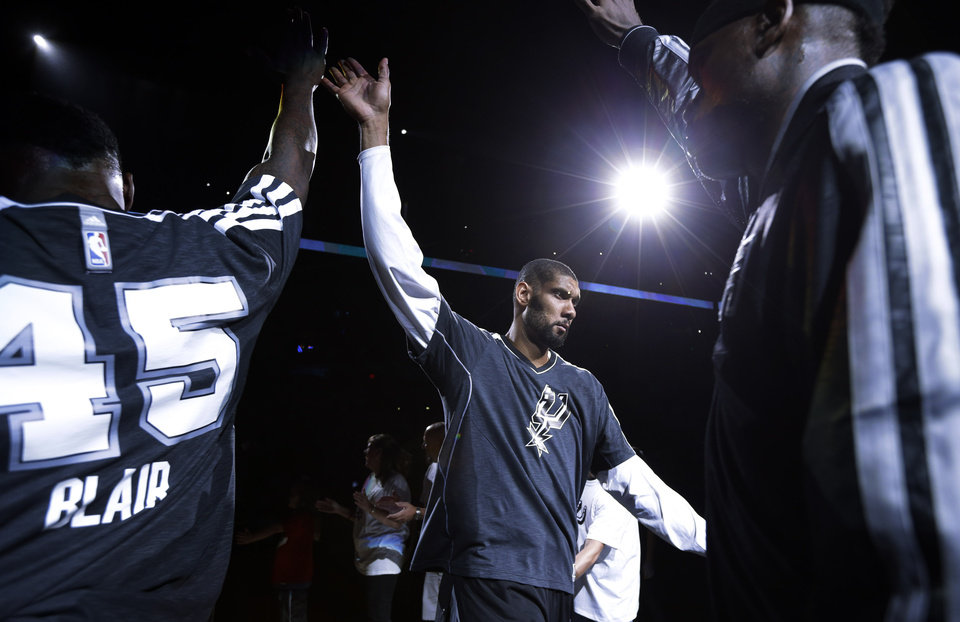 Photo - San Antonio Spurs' Tim Duncan, center, takes the court as he is introduced in the team's home opener of an NBA basketball game against the Oklahoma Thunder, Thursday, Nov. 1, 2012, in San Antonio. (AP Photo/Eric Gay) ORG XMIT: TXEG108