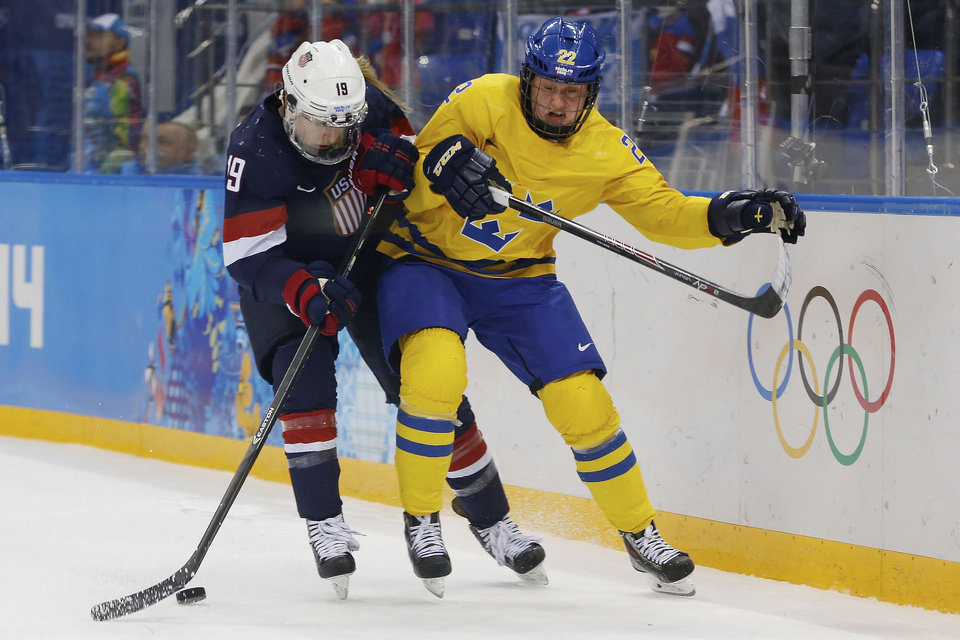 Photo - Gigi Marvin of the United States and Emma Eliasson of Sweden battle fro control of the puck during the second period of the 2014 Winter Olympics women's semifinal ice hockey game at Shayba Arena Monday, Feb. 17, 2014, in Sochi, Russia. (AP Photo/Petr David Josek)