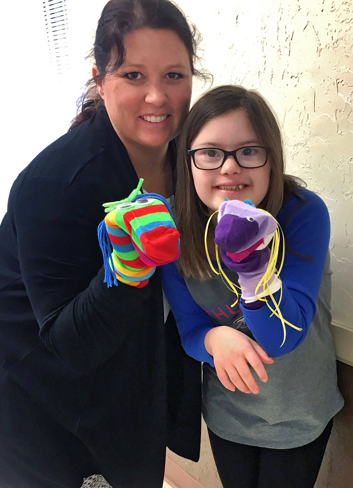 Photo - Leslee Boswell and Drew Boswell pose with the crazy sock puppets they made at the Cleveland County 4-H workshop held in Norman. [PHOTO PROVIDED]
