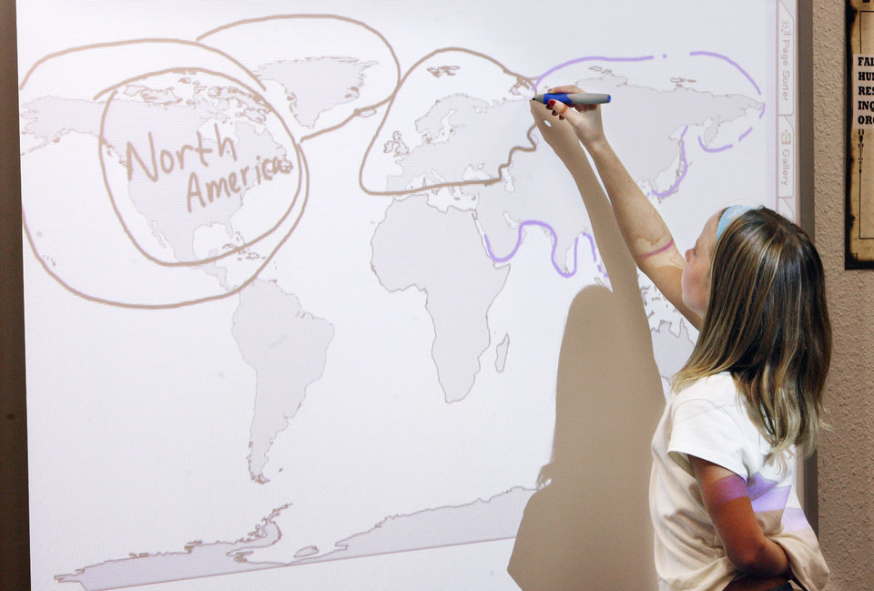 Fourth-grader Lauren Scott, 10, tracing Asia on the Smartboard during a world geography lesson in Lisa Stroble\'s fourth-grade class at Deer Creek Elementary School in the Deer Creek School District in Okla. City Monday, August 28, 2006. By Paul B. Southerland, The Oklahoman
