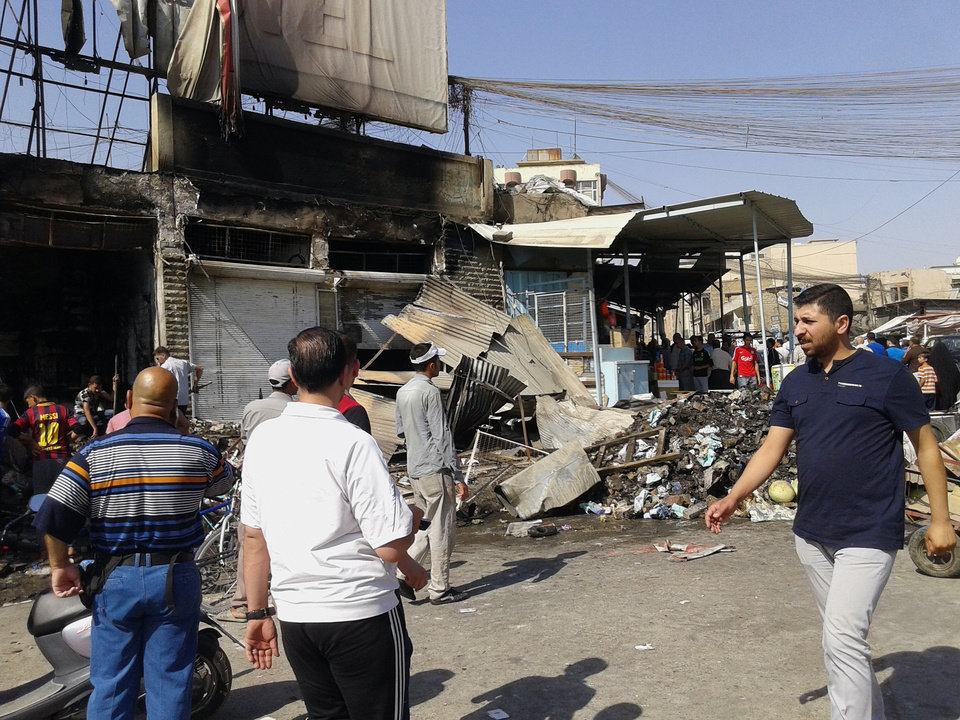 Photo - People inspect buildings damaged by an Iraqi government airstrike in the northern city of Mosul, Iraq, Saturday, June 28, 2014. The Iraq military carried out three airstrikes on the insurgent-held city of Mosul early Saturday. (AP Photo)
