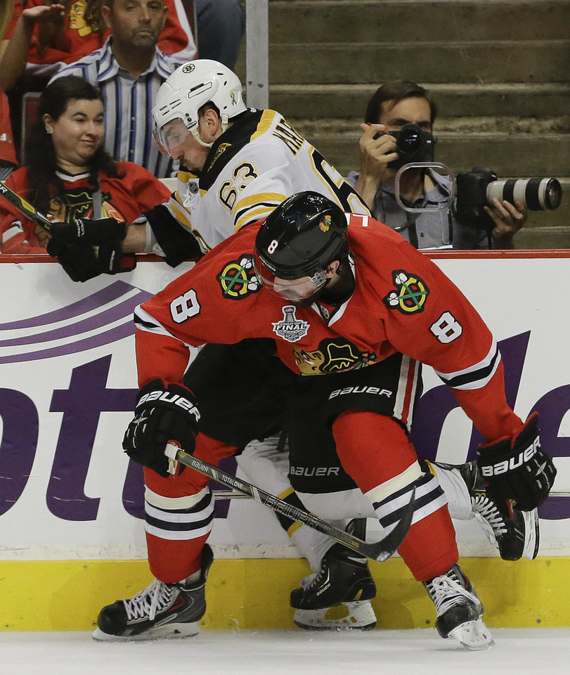 Photo - Chicago Blackhawks defenseman Nick Leddy (8) gets tangled up with Boston Bruins left wing Brad Marchand (63) in the second period during Game 2 of the NHL hockey Stanley Cup Finals, Saturday, June 15, 2013, in Chicago. (AP Photo/Nam Y. Huh)