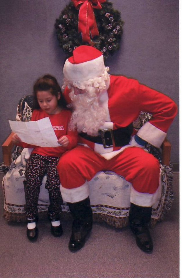 Photo - Drue Woodmansee, 7, shows Santa her Christmas list at last year's Santa Shots. PHOTO PROVIDED BY EDMOND POLICE DEPARTMENT   ORG XMIT: 0811241624283030