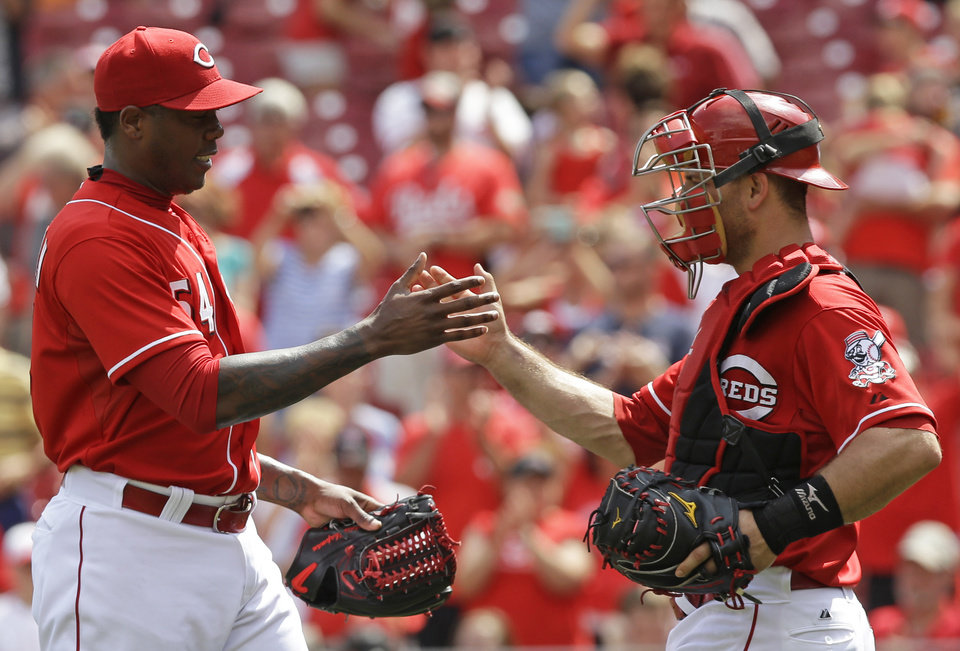 Photo - Cincinnati Reds relief pitcher Aroldis Chapman, left, is congratulated by catcher Devin Mesoraco after they defeated the Chicago Cubs 4-2 in a baseball game, Tuesday, July 8, 2014, in Cincinnati. Chapman earned his 18th save. (AP Photo/Al Behrman)