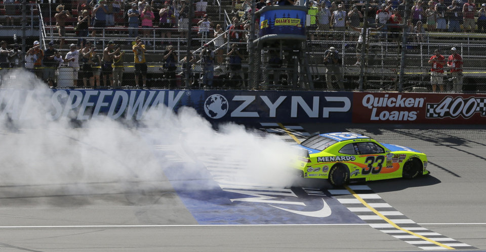 Photo - Driver Paul Menard burns rubber after winning the NASCAR Nationwide series auto race at Michigan International Speedway in Brooklyn, Mich., Saturday, June 14, 2014. (AP Photo/Carlos Osorio)
