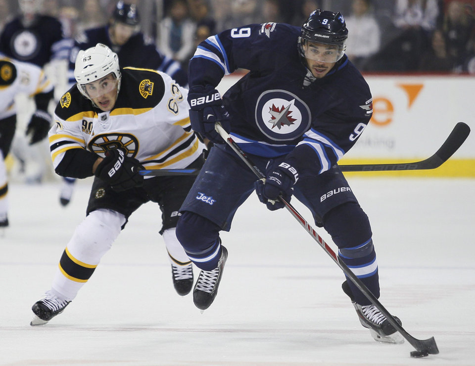 Photo - Boston Bruins' Brad Marchand (63) chases down Winnipeg Jets' Evander Kane (9) during the second period of an NHL hockey game Thursday, April 10, 2014, in Winnipeg, Manitoba. (AP Photo/The Canadian Press, John Woods)