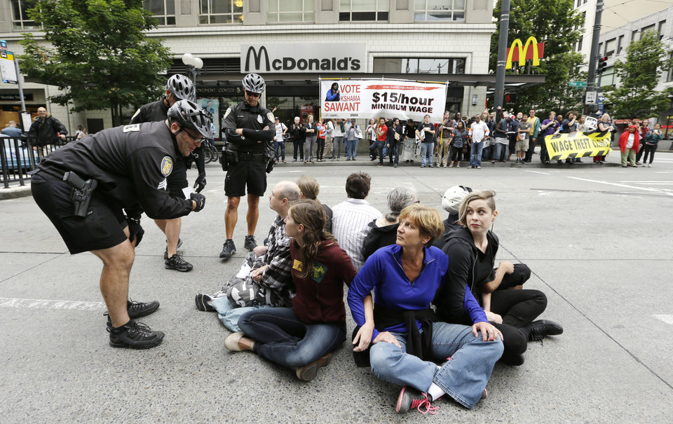 Photo - FILE -- In this Aug. 1, 2013 file photo, a Seattle police officer leans in to explain the arrest procedure to a group of eight protesters blocking a downtown intersection across from a McDonald's restaurant in downtown Seattle. Seattle police said they made several arrests at the demonstration protesting what marchers say are low wages and improper treatment for fast-food workers. Washington already has the nation's highest state minimum wage at $9.19 an hour. Now, there's a push in Seattle, at least, to make it $15. That would mean fast food workers, retail clerks, baristas and other minimum wage workers would get what protesters demanded when they shut down a handful of city restaurants in May and others demonstrated nationwide in July. (AP Photo/Elaine Thompson, File)