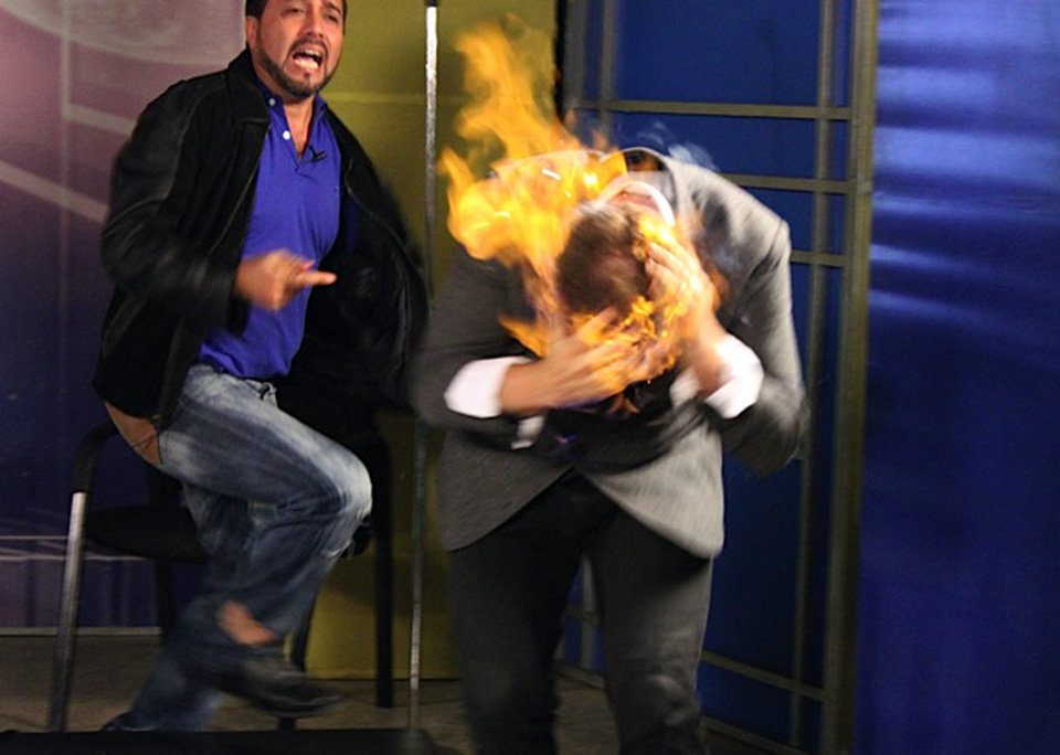 Photo - In this picture released by American magician Wayne Houchin, Dominican TV presenter Franklin Barazarte, left, reacts as Houchin's head burns while taping