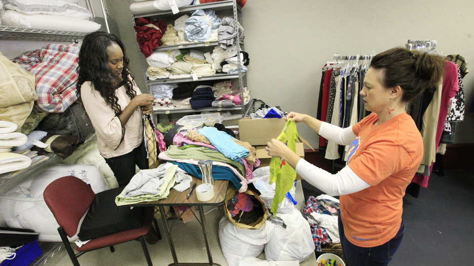 Photo -  Volunteers Edna Kyerematen of Oklahoma City and Amy Burleson of Edmond, sort donated clothing at Carina's Closet, a free clothing distribution site operated by No Boundaries International. Photo by Paul B. Southerland, The Oklahoman   PAUL B. SOUTHERLAND -  PAUL B. SOUTHERLAND